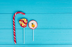 Three colorful lollipops on wooden turquoise table Royalty Free Stock Image