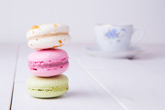 Three colorful macaroons with cup of tea Stock Photos