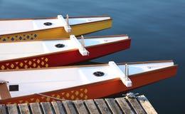 Three colorful paddle boats at a dock Stock Photos