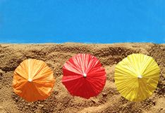 Three colorful parasols at the beach, top view Royalty Free Stock Image