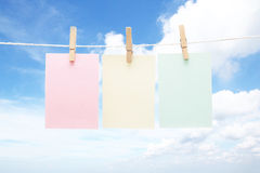 Three colorful pastel notes on pegs Stock Photos