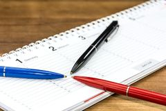 Three pens on a schedule with captions of the days of the week in German pointing to one date. Three colorful pens on a schedule with captions of the days of the royalty free stock photo