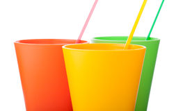 Three colorful plastic cups with straws isolated on white. Background Royalty Free Stock Photography