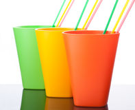 Three colorful plastic cups with straws on white. Background Stock Photo