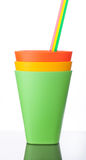 Three colorful plastic cups with straws on white. Background Stock Image