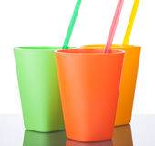 Three colorful plastic cups with straws on white. 