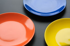 Three colorful plates on blackbackground Stock Photos