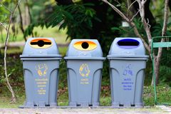 Three colorful recycle bins in the park. Can, plastic bottle, paper bag recycle bin, glass bottle recycle bin and waste, food waste bin Royalty Free Stock Photos