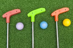 Three Mini Golf Clubs With Balls. Three colorful rubber golf clubs with balls for miniature golf royalty free stock image