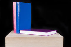 Three colorful school books on a wooden table Royalty Free Stock Image
