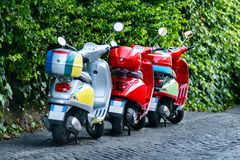 Three colorful scooters at the street, Rome, Italia. New old motorino, best transport for travel by Rome royalty free stock photography
