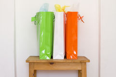 Three colorful shopping bags on a wooden table. Green, white and orange shopping bags interior on a wooden table Royalty Free Stock Photography