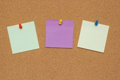 Three colorful sticky notes with pushpins and blank space, isolated on cork background, school concept stock photo