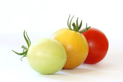 Three colorful tomatoes on white background. Close up view - row of three colorful - green, orange and red - tomatoes on white background Royalty Free Stock Image