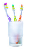 Three colorful toothbrushes in glass Royalty Free Stock Photo