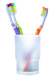 Three colorful toothbrushes in glass, two against one Stock Photo