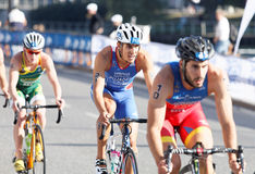 Three colorful triathletes cycling Royalty Free Stock Photography