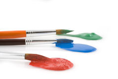 Three colors with brushes. Brushes with green, blue and red paint Royalty Free Stock Photography