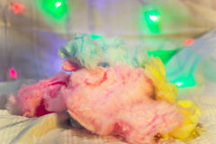 Three colors of cotton candy close-up. Pink blue and yellow colored cotton candy on a background of illuminations close-up Royalty Free Stock Images