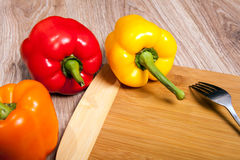 Three colors the peppers on wood cutting background with fork. Yellow, orange and red peppers. Royalty Free Stock Image