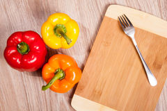 Three colors the peppers on wood cutting background with fork. Yellow, orange and red peppers. Royalty Free Stock Images