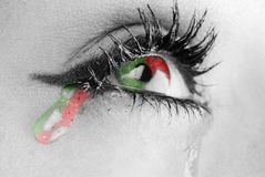 Three colors tears. Close up on the eyes of a young woman with three colors tears Stock Photo