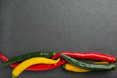 Three colors chili peppers on a dark background Stock Photos