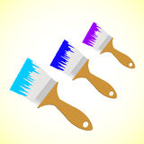 Three colour paint brushes on yellow smooth backgr Royalty Free Stock Image