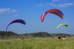 Three colour paraglide. Rs on the green meadow stock images