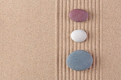 Three coloured pebbles on raked sand. Three coloured pebbles on a raked sand zen garden Royalty Free Stock Image