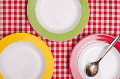 Three coloured plates and a spoon Royalty Free Stock Images