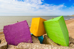 Three colourful blocks of a concrete breakwater by the sea. Royalty Free Stock Photo