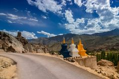 Three colourful buddhist religious stupas. At Leh, Ladakh, Jammu and Kashmir, India. A road passing through. Shot under daylight with blue sky and white clouds stock image