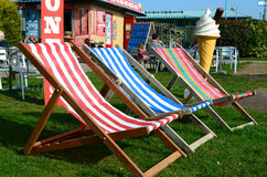 Three colourful deck chairs. Three empty deck chairs outside a ice cream cafe on a sunny day Stock Image