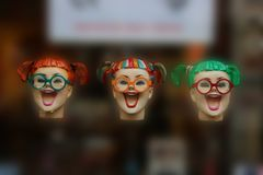 Three colourful fake laughing woman heads floating midair with different haircuts royalty free stock photography