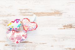 Multiple colourful hearts on vintage wooden background. Three colourful handmade colourful hearts on a wooden retro vintage background Royalty Free Stock Image