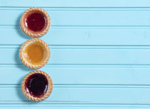 Three colourful jam tarts on a blue background Stock Images