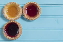 Three colourful jam tarts on a blue background Stock Image