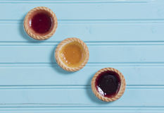 Three colourful jam tarts on a blue background Stock Photo