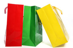 Three colourful paper shopping bags. In red, green and yellow suitable for recycling standing on a white background royalty free stock image