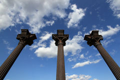 Three columns. Three bronze columns with clouds and sky Royalty Free Stock Images