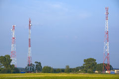 Three communication towers. On blue sky background Stock Photos
