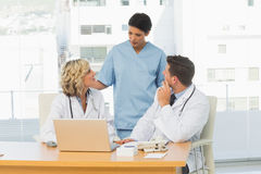 Three concentrated doctors in discussion Royalty Free Stock Photos