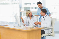 Three concentrated doctors using computer together Royalty Free Stock Image