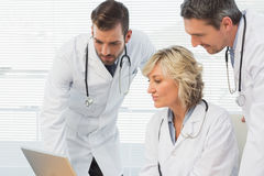Three concentrated doctors using laptop together Stock Image