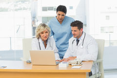 Three concentrated doctors using laptop together Stock Photos