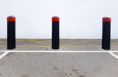 Concrete security bollards, vehicle crash barriers in a parking lot. Three concrete bollards set against a white wall in a parking lot stock photos