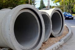 Three concrete pipes lie on the unfinished sidewalk near the road at the site of the road construction works in the city. During the day royalty free stock photos