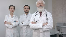 Three confident clinicians in white coats looking at camera. stock footage
