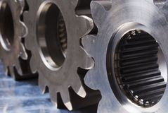 Three connecting gears. Sideview of three cogs, gears against stainless-steel Stock Images